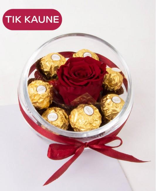 Mieganti rožė stikliniame inde su braškėmis ir saldainiais